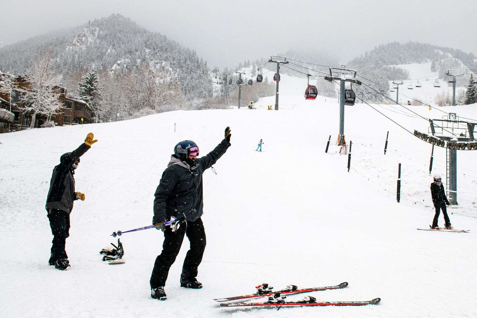 Aspen Skiing Company employees wave to friends at the base of Aspen Mountain the day before the official opening of the mountains in Aspen on Tuesday, Nov. 24, 2020. Aspen Skiing Company employees and family had the opportunity to ski Aspen and Snowmass after a fresh snowfall. (Kelsey Brunner/The Aspen Times)