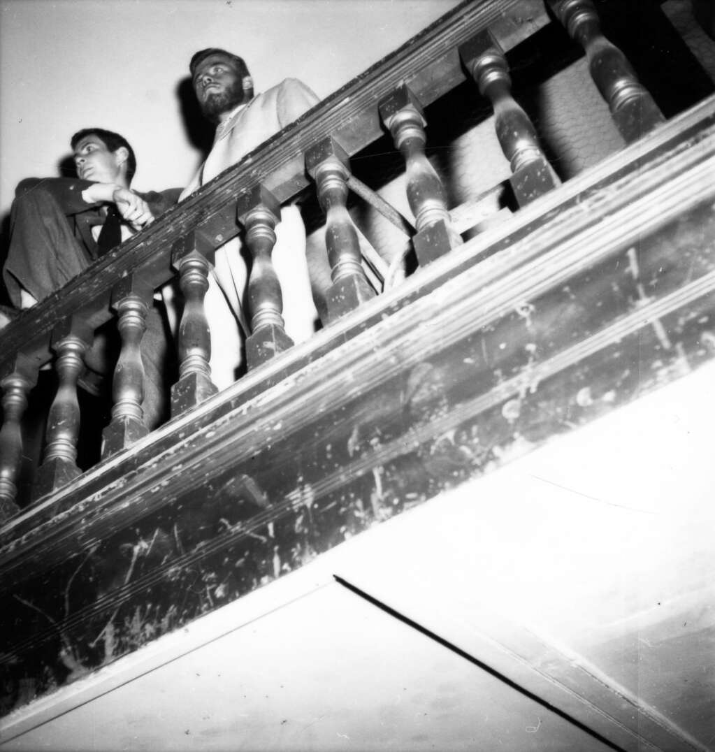 One b/w photograph taken during a cowboy dance held in the Armory (City Hall) in Aspen on August 14, 1949.  Two men are standing at the edge of the balcony bannister and looking out.  The photograph is taken from a floor below and looking up at the men. Aspen Historical Society, Berko Collection