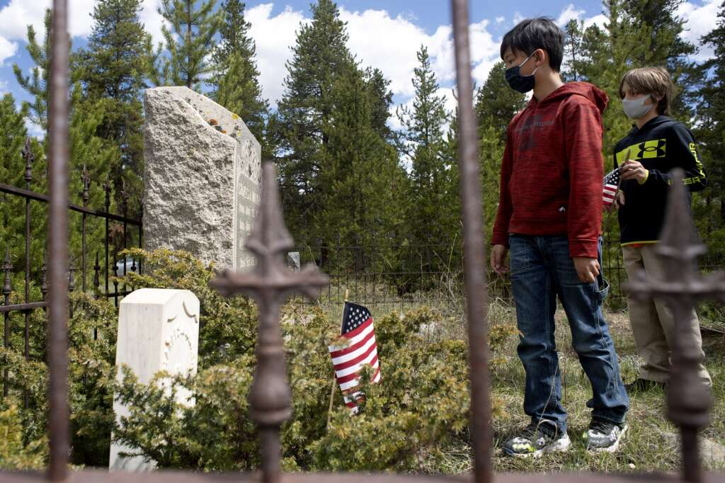 Nicholas George, left, and Jaxson Zimsky, fourth graders from Upper Blue Elementary School read a veteran's name off of a tombstone while visiting the Valley Brook Cemetery in Breckenridge during a class field trip on Friday, May 28. Forth grade students placed flags at the graves of veterans throughout the cemetery in preparation for Memorial Day. | Jason Connolly / Jason Connolly Photography