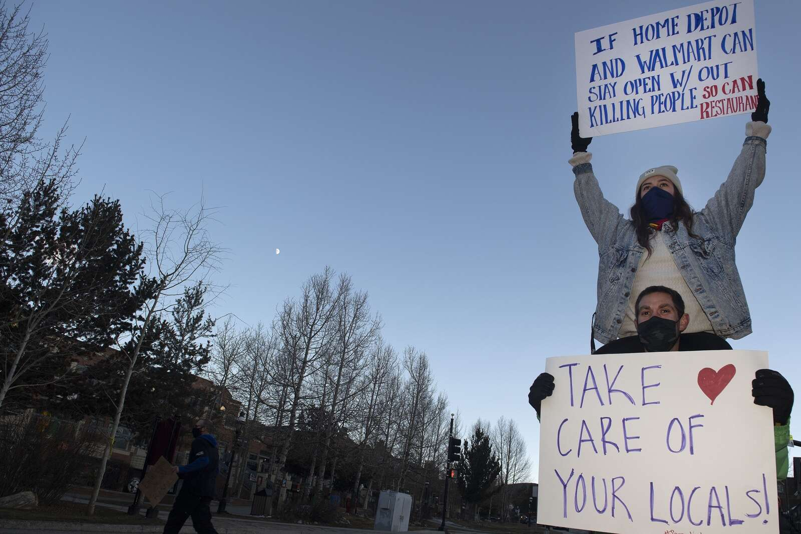 Ginger Perez, an employee at Downstairs at Eric's in Breckenridge, sits on the shoulders of Kyle Rocco on Monday, Nov. 23, while protesting the prohibition of in-person dining at restaurants.