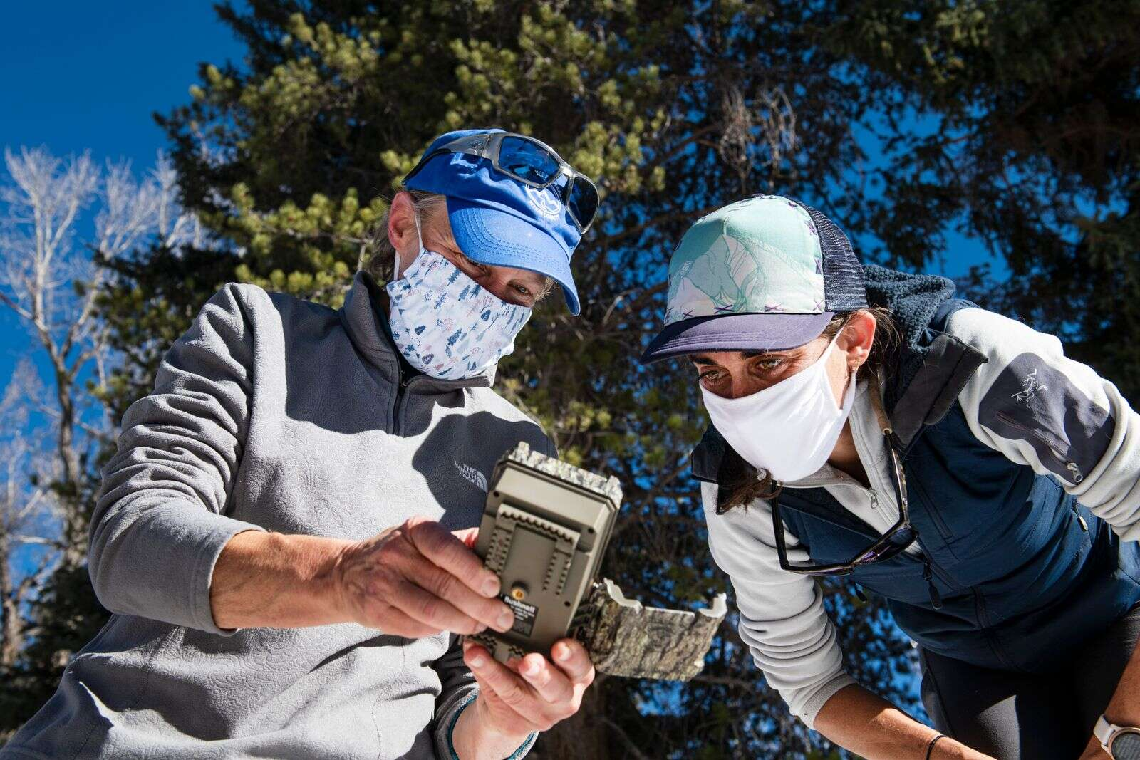 Pitkin County Open Space & Trails' Janet Urquhart shows Liza Mitchell how to work the camera that the two set out to monitor dam activity at Northstar Nature Preserve on Wednesday, Dec. 9, 2020. (Kelsey Brunner/The Aspen Times)