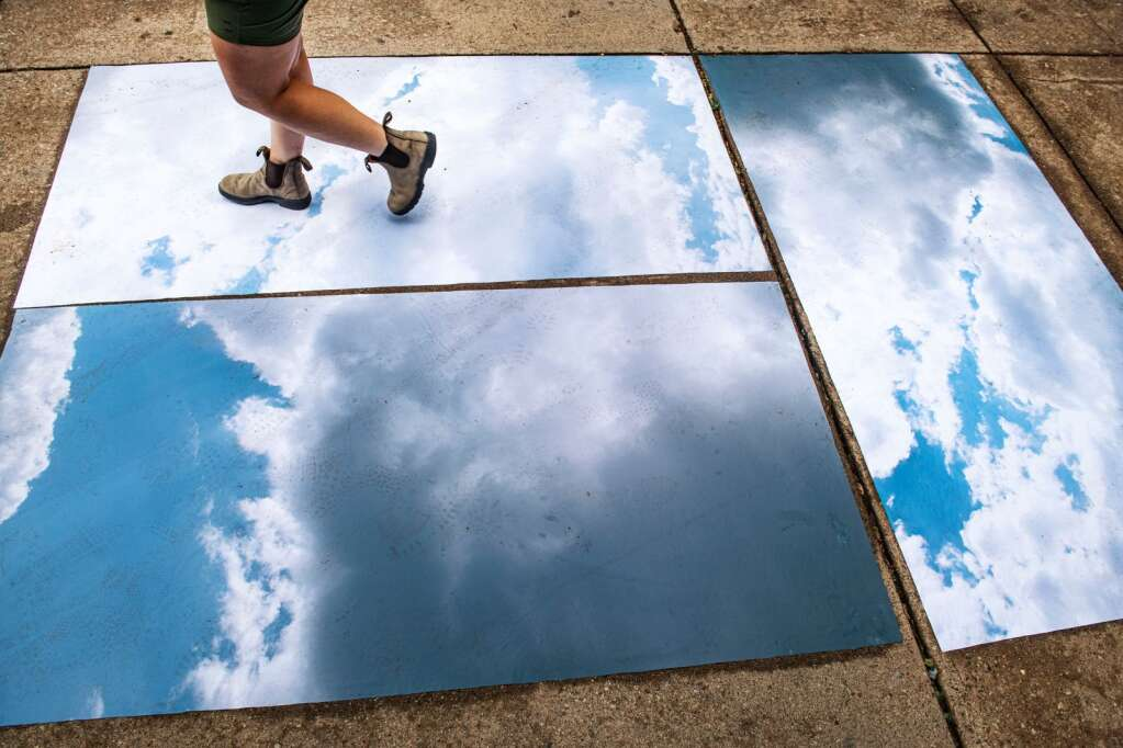A woman walks through the large-scale image of Esther Nooner at Snowmass Mall for the town's art walk on Thursday, June 24, 2021 (Kelsey Brunner / The Aspen Times)