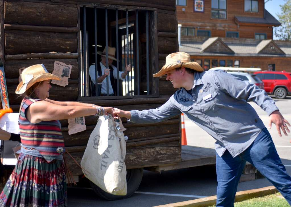 A man offers a donation to keep the prisoner in jail on Saturday as part of a fundraiser hosted by Taking Steps for Cancer.   Amy Golden / agolden@skyhinews.com