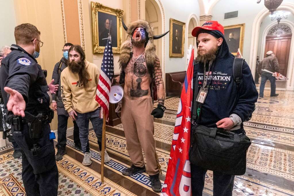 Supporters of President Donald Trump are confronted by Capitol Police officers outside the Senate Chamber inside the Capitol, Wednesday, Jan. 6, 2021 in Washington. (AP Photo/Manuel Balce Ceneta)