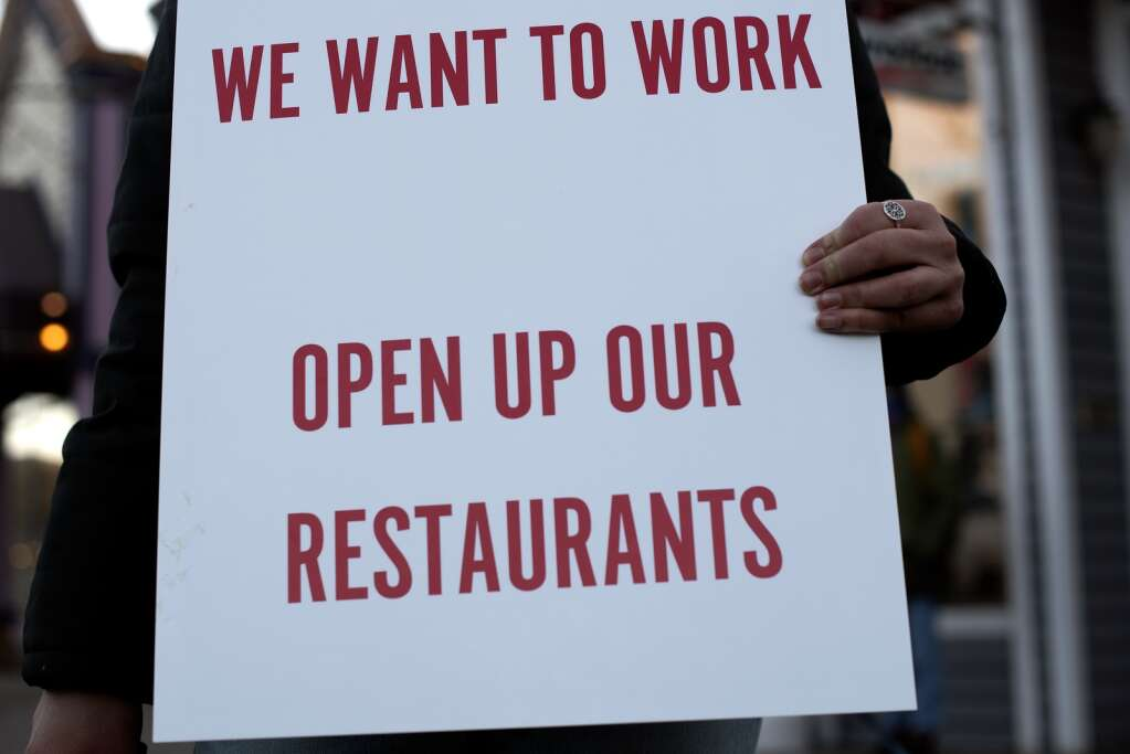A Summit County service industry worker holds a sign Monday, Nov. 23, while protesting the prohibition of in-person dining at restaurants.