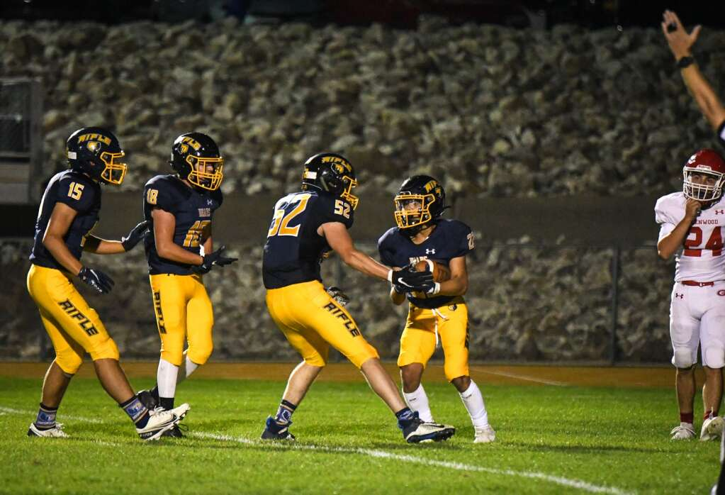 The Rifle Bears celebrate after being the first to score in the 3rd quarter during Friday night's rivalry game against the Glenwood Springs Demons.  Chelsea Self / Post Independent