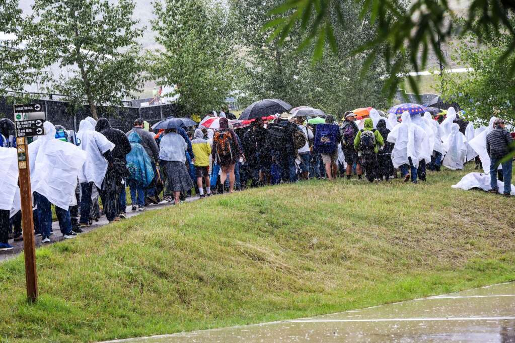 People wait in line during a brief downpour to get inside the concert venue for Jazz Aspen Snowmass on Friday, Sept. 3, 2021, in Snowmass Village. Photo by Austin Colbert/The Aspen Times.