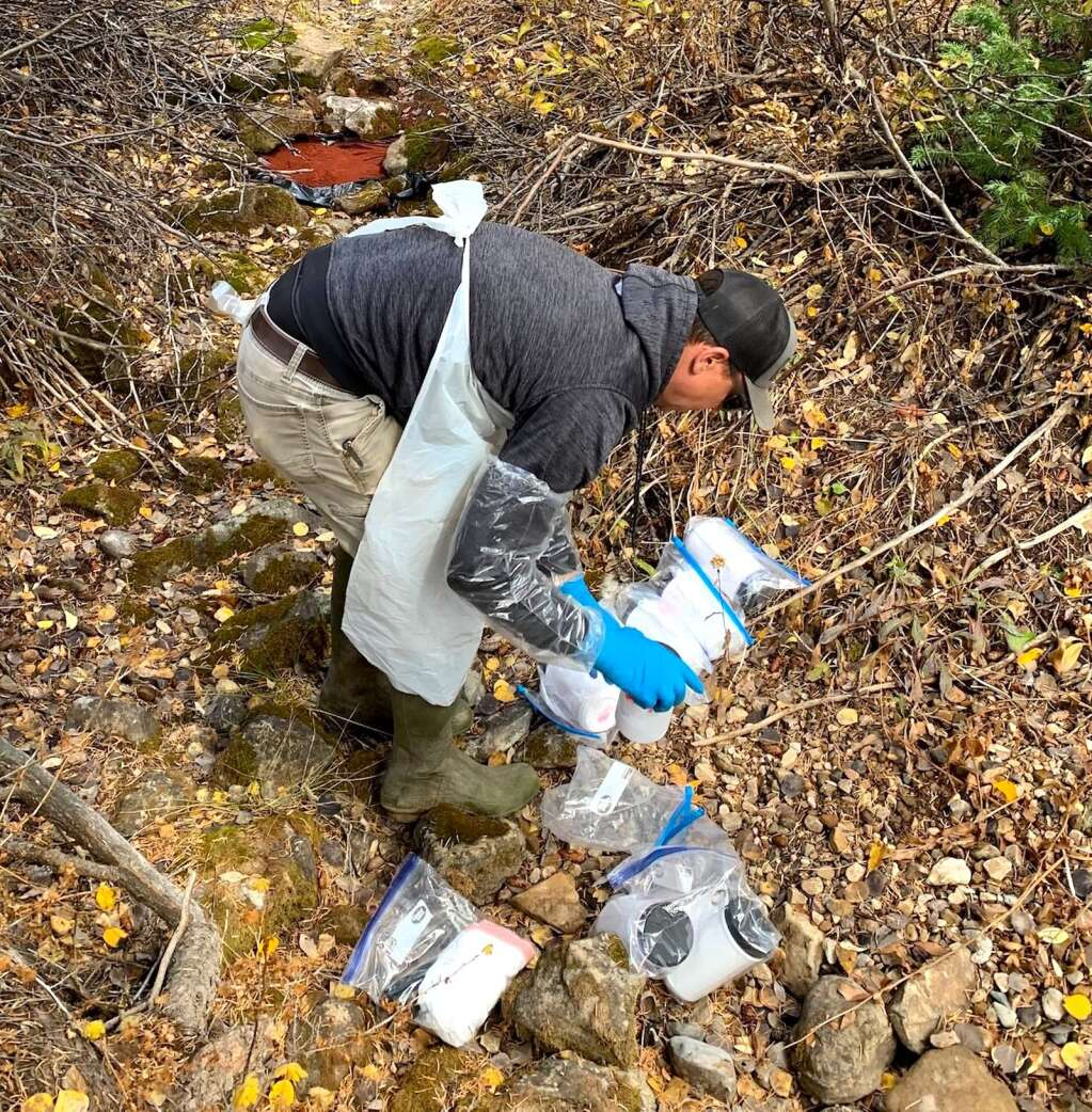 Senior Project Scientist Dave Woods introduces dye at West Fork Deadhorse Creek. | Erin Dundas/White River National Forest