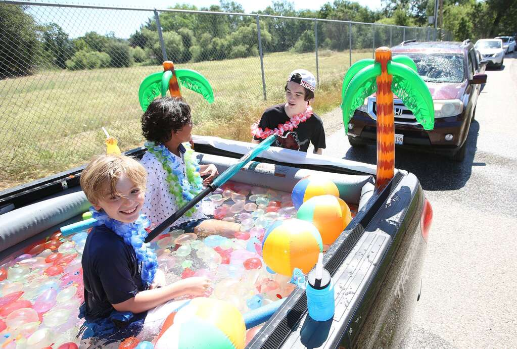 Members of the Zimmerman family kept cool in the back of a pickup truck turned into a pool filled with water balloons during Thursdays Ready Springs Elementary School drive-thru graduation ceremony. | Photo: Elias Funez