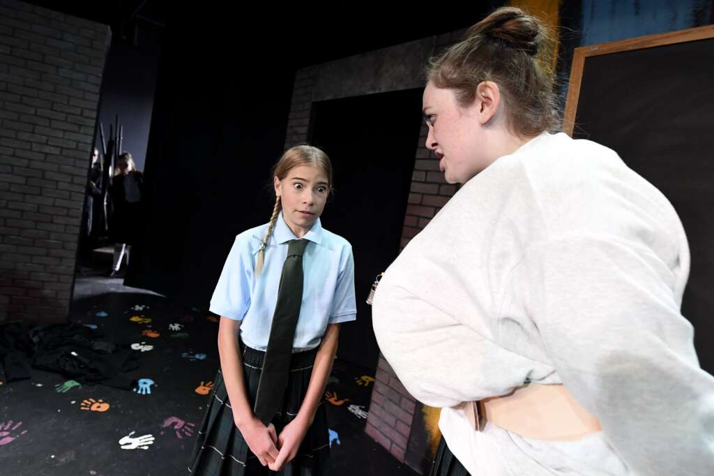 Mikaela Clark, right, who plays headmistress Miss Trunchbull, reprimands actress Peyton Goossen as they perform a scene during a dress rehearsal of the musical