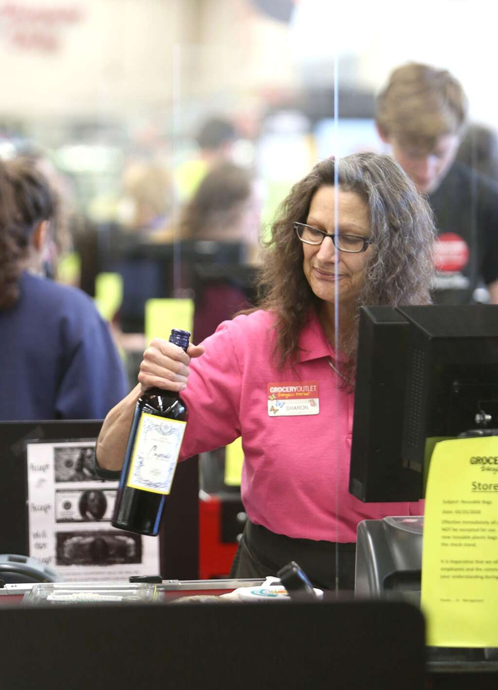 Grass Valley Grocery Outlet checker Sharon Lolli works from behind a plexiglass screen recently installed at checkout aisles to better help protect workers April 1.| Photo: Elias Funez