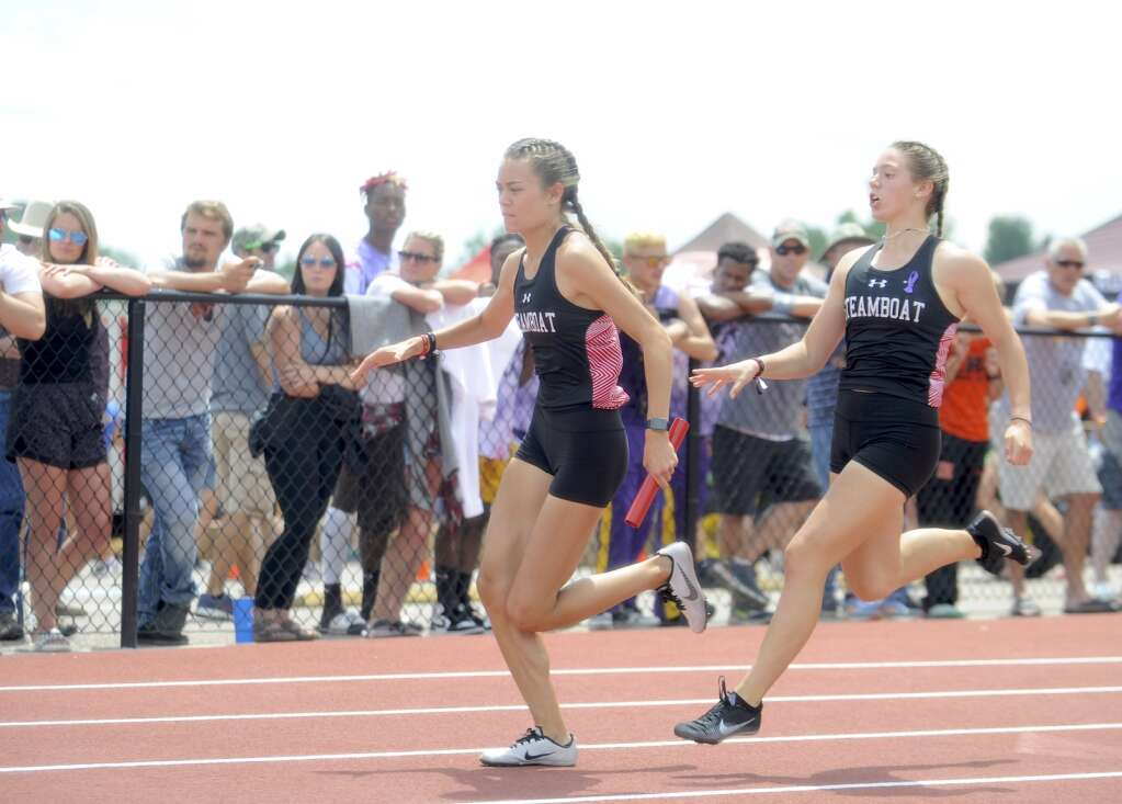 Steamboat Springs junior Elise Colby passes the baton to junior Kelsey Hamilton during the 800 sprint medley relay at the CHSAA Track and Field State Championships at JeffCo Stadium on Friday. (Photo by Shelby Reardon)