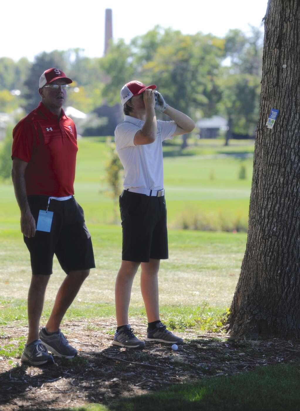 Steamboat Springs junior golfer Jeremy Nolting and Sailors head coach Andrew Donner evaluate a shot from near some trees at the 4A State Golf Championships at City Park Golf Course on Tuesday afternoon.   Shelby Reardon/Steamboat Pilot & Today