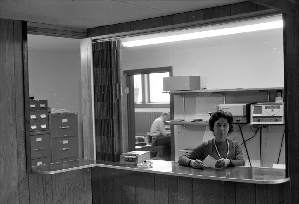 One b/w negative of the interior of the Aspen City Hall following a remodel, 1967. Shown here is part of the enlarged lobby with the new indoor police information window. The woman is identified as Mrs. Logan Bailor. This image is in the Aspen Illustrated News on March 16, 1967 (page 2). Aspen Historical Society, Hiser Collection