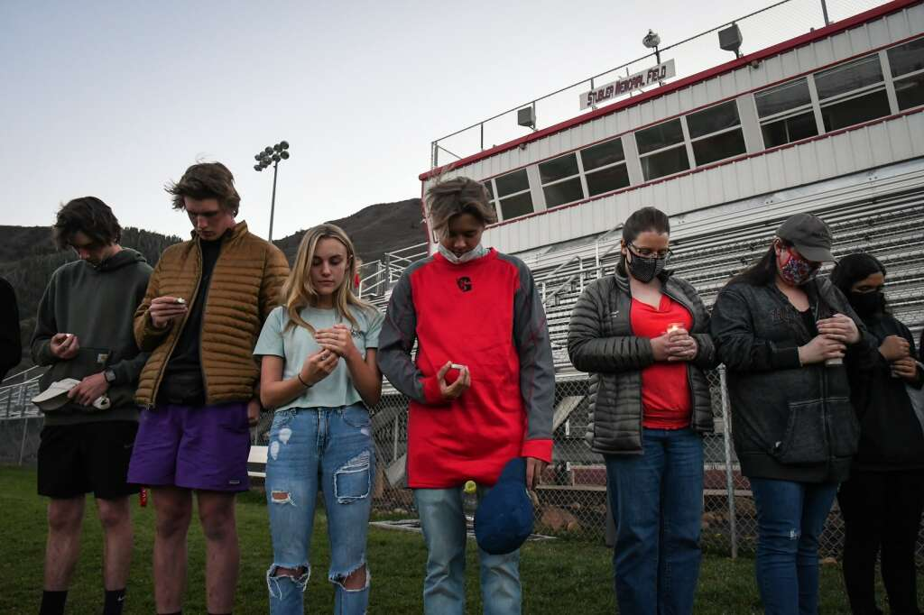 Students and friends of Jim Benson lower their heads in prayer at the start of the candle light vigil in remembered of the late Benson who passed away last Saturday.  Chelsea Self / Post Independent