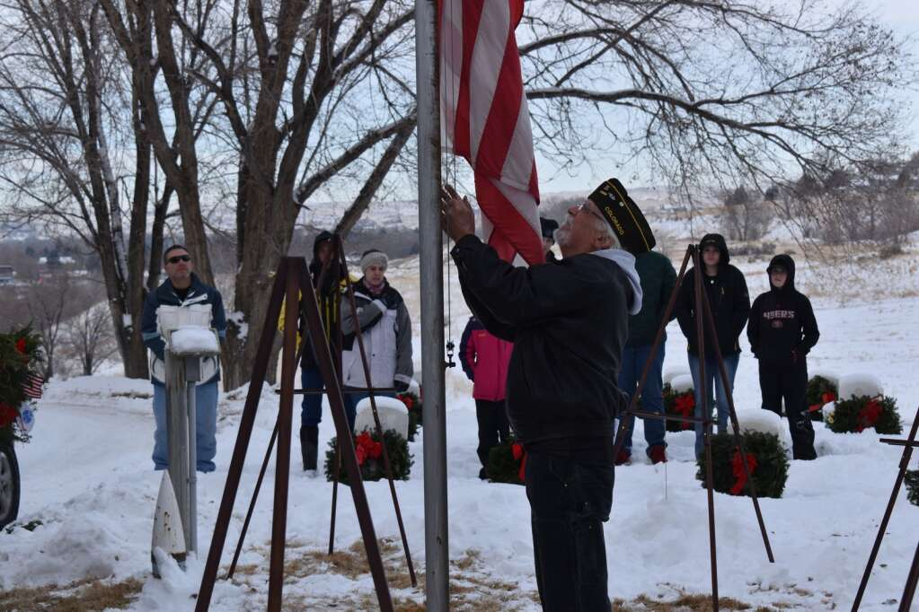 Ron Epplin lowers the American Flag Saturday during the Wreaths Across America ceremony.
