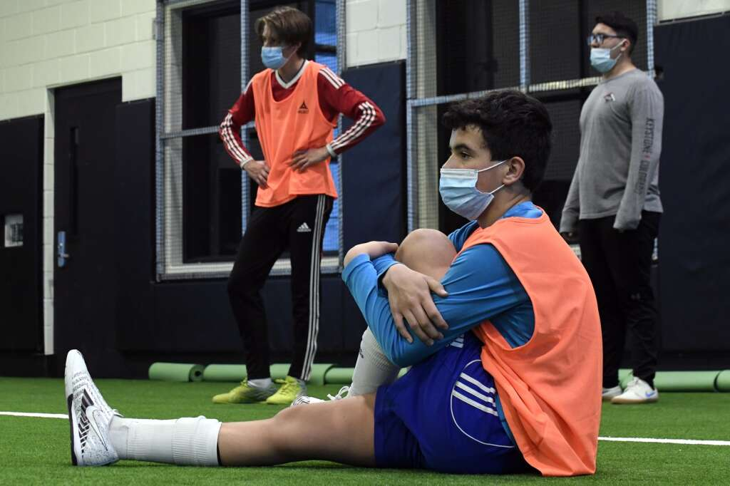 Summit High School boys varsity soccer player Owen Gallo stretches during indoor practice at Summit High on Tuesday, March 16. | Photo by Jason Connolly / Jason Connolly Photography