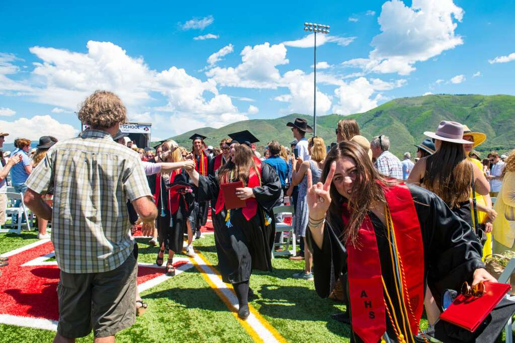 """Aspen Graduates process out of the football stadium after the ceremony with Evelyn Leibinger giving the """"rock on"""" sign as she walks out on Saturday, June 5, 2021. (Kelsey Brunner/The Aspen Times)"""