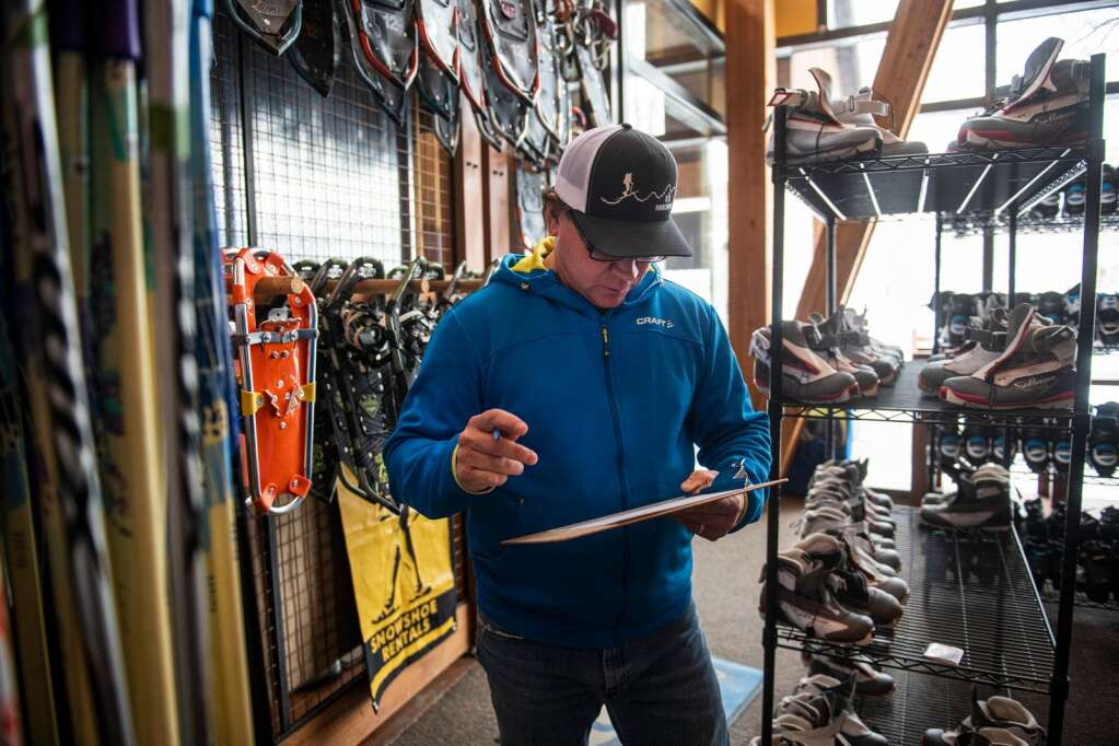 Snowmass Cross Country Center manager Scott Nelson looks over a rental sheet in the shop in Snowmass on Friday, January 3, 2020. (Kelsey Brunner/The Aspen Times)