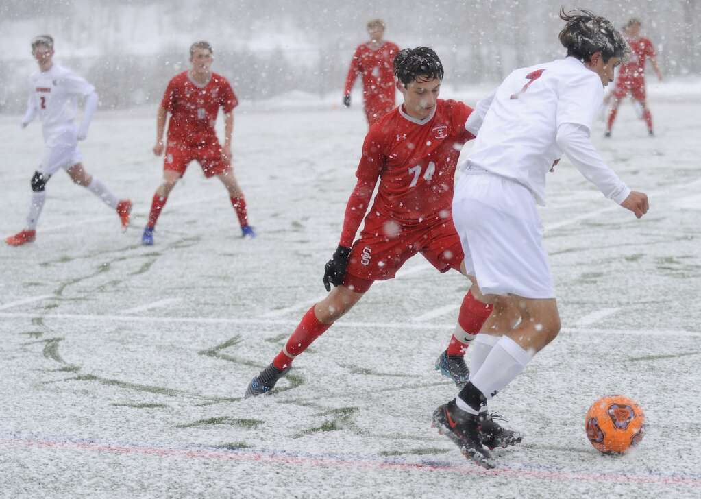 Steamboat Springs junior Liam Catterson keeps himself between his opponent and the goal during a snowy game against Glenwood Springs on Thursday evening. (Photo by Shelby Reardon)
