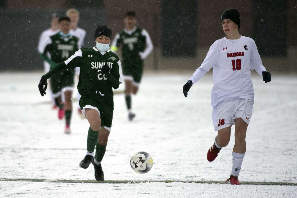 Summit High sophomore midfielder Owen Gallo McMahon races Glenwood Springs Demon Justin Garces to the ball during a snowy senior nightmatch at Climax Molybdenum Field at Tiger Stadium on April 15, 2021. The Tigers defeated the Demons 4-0. | Photo by Jason Connolly / Jason Connolly Photography