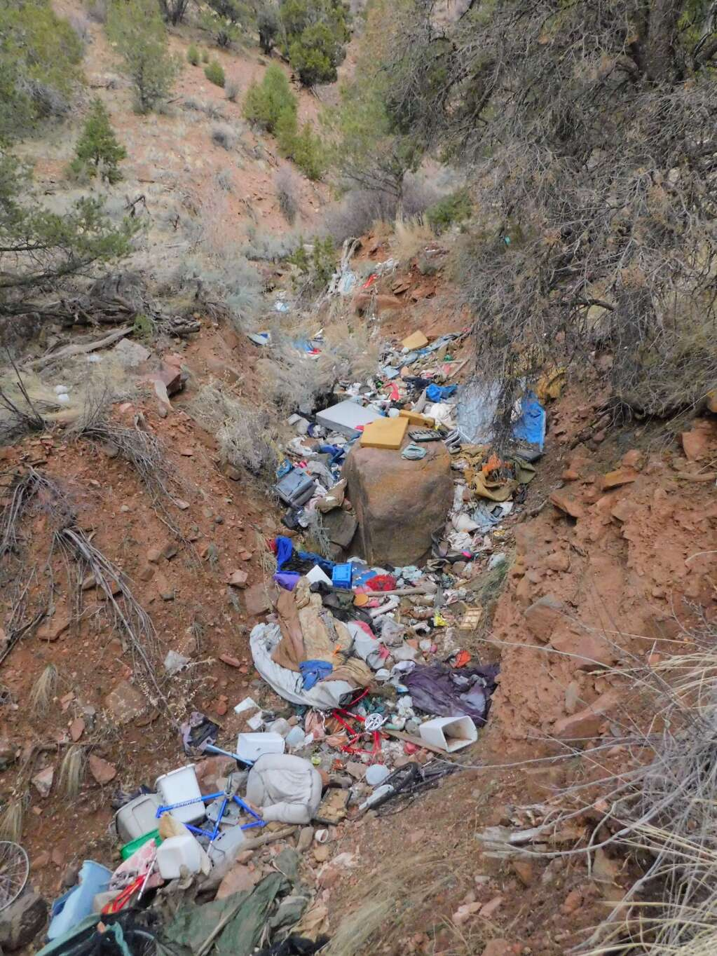 Piles of trash line the thickets and ravines on the hillside east of Walmart in Glenwood Springs where homeless camps have been located for several years.