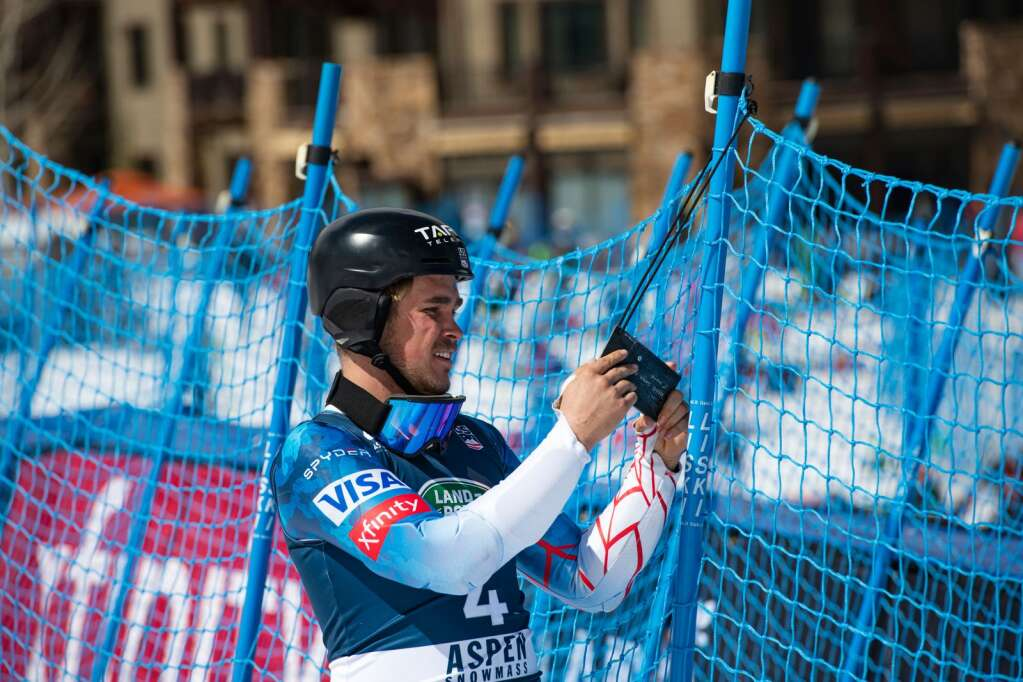 Third place finisher River Radamus looks at his medal as it hangs on the boundary fence after the second run of the U.S. Alpine Championships at Aspen Highlands on Wednesday, April 7, 2021. (Kelsey Brunner/The Aspen Times)