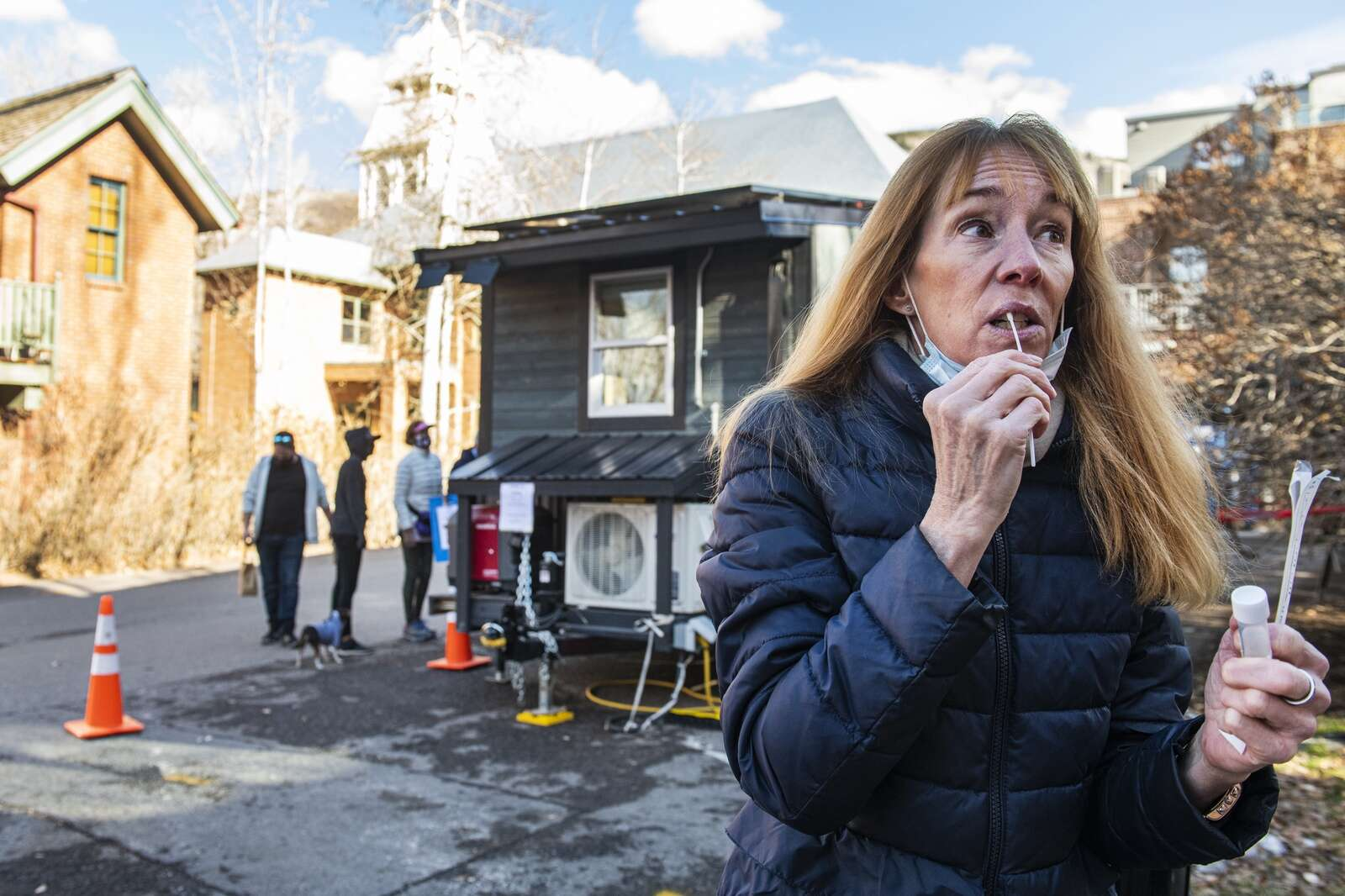 Colleen Delia self-administers a free COVID-19 swab test behind City Hall in Aspen on Monday, Nov. 23, 2020. The tests are free and available five days a week to anyone wanting to be tested. On December 1, they plan to open for testing seven days a week. Delia took the test before flying home to see her father for the holiday. She has no symptoms, but wanted to take precautions before visiting family. (Kelsey Brunner/The Aspen Times)