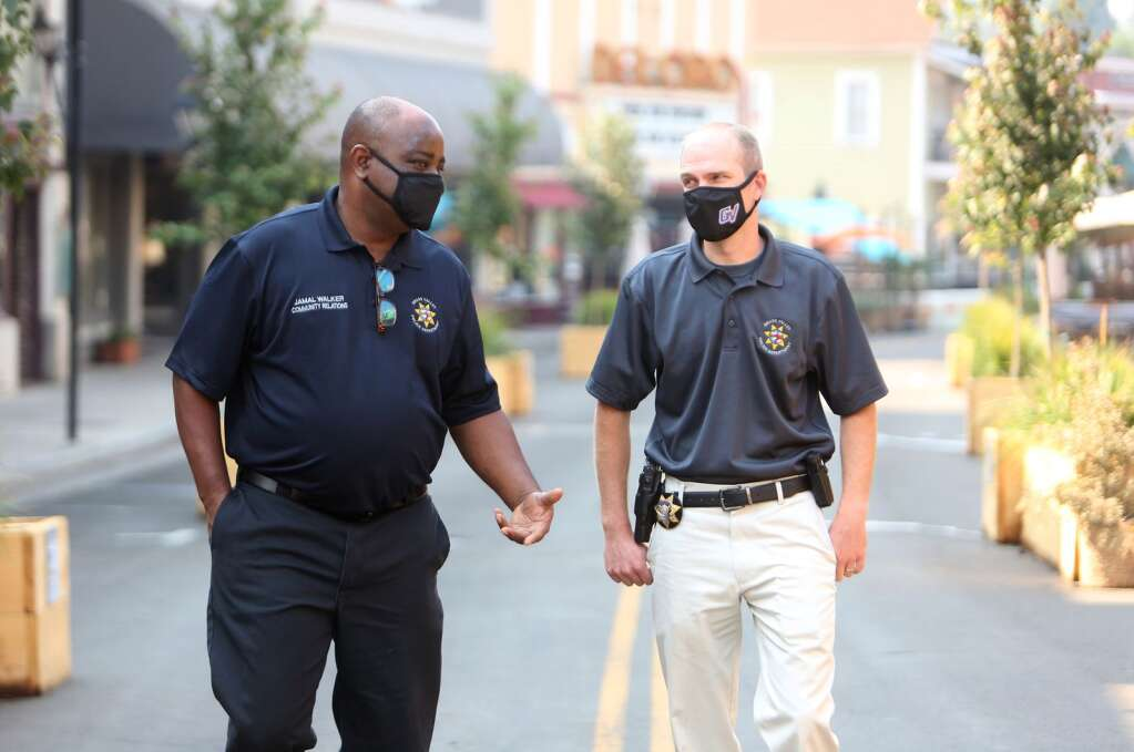 Community Relations Coordinator Jamal Walker and Chief Alex Gammelgard share a few words as they walk along Mill Street Friday morning Aug 29.