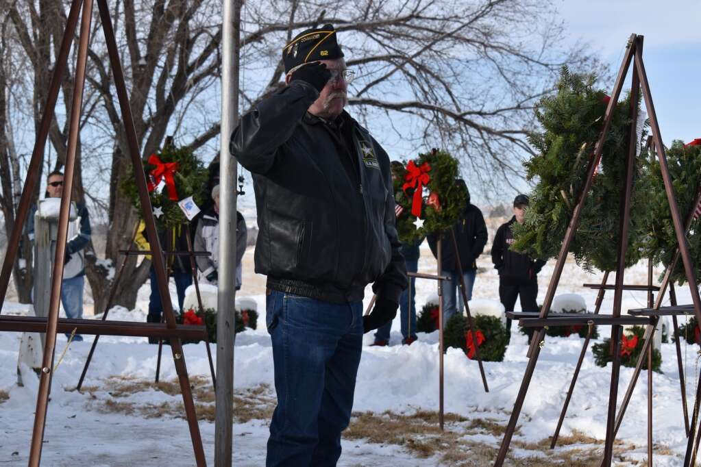 Ed Wilkinson, an Army veteran, salutes a wreath that he placed Saturday.