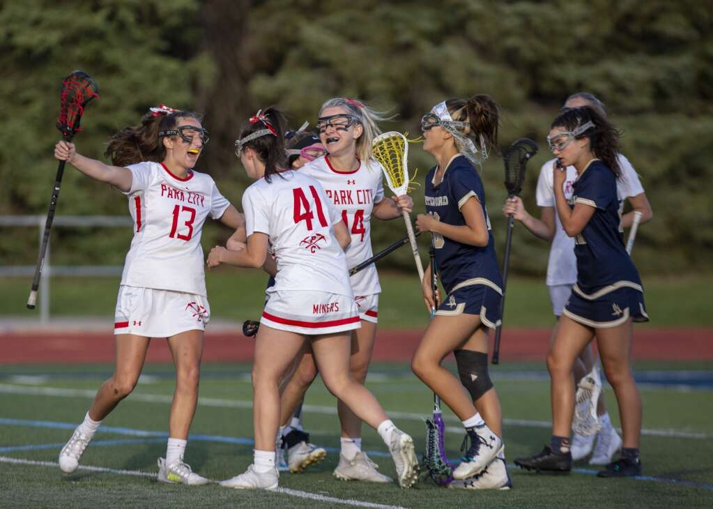 Park City High School sophomore Lilly Hunt (13) runs to hug junior teammate Sam Riely (41) after the Miners score against Waterford. (Tanzi Propst/Park Record)