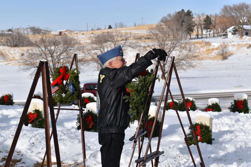 Michael Lausin places a wreath Saturday for the Coast Guard.