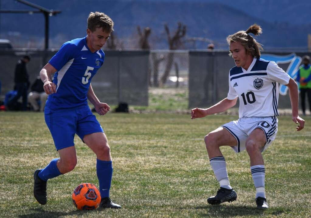 Coal Ridge Titan Jack Price tries to dribble the ball past the defending Vail Mountain Gore Ranger during Tuesday afternoon's game at Coal Ridge High School. |Chelsea Self / Post Independent