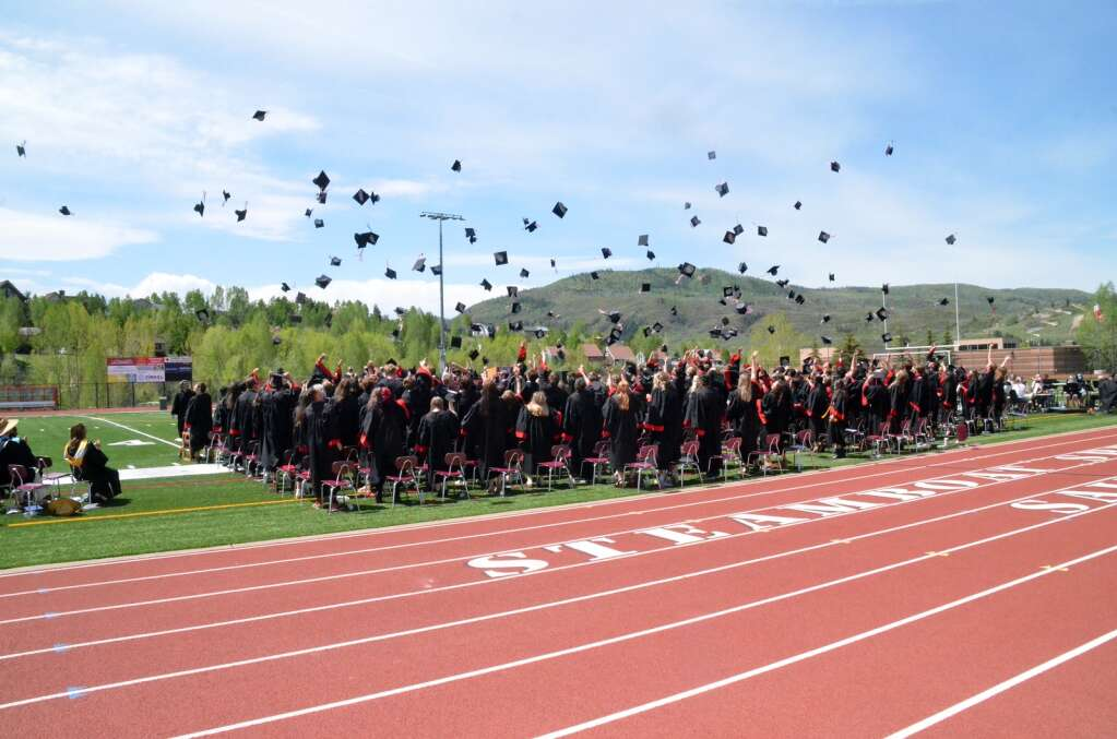 The obligatory tossing of the cap. (Photo by Bryce Martin)