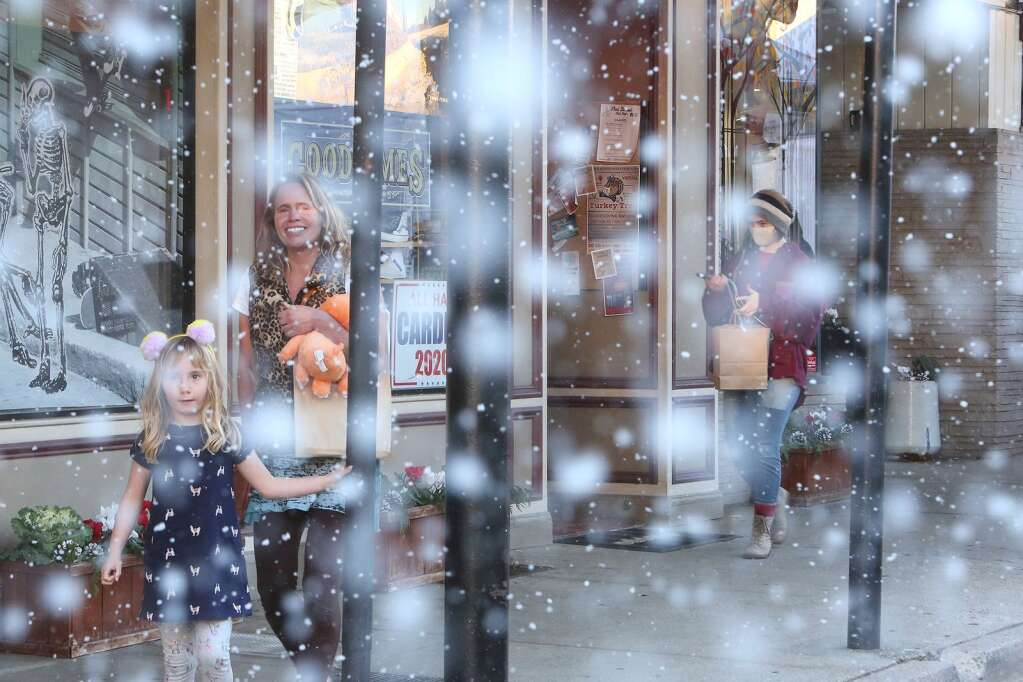 Snow from a pair of snow machines installed above Stucki Jewelers along Mill Street help to bring a little holiday cheer to the downtown shopping scene Nov 29. | Photo: Elias Funez