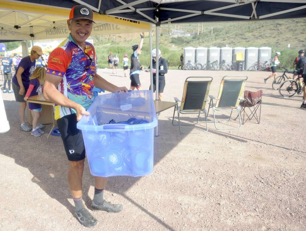 Pablo Hadzeriga restocks pop-up snack bowls at the Stagecoach aid station as part of the Tour de Steamboat Springs on Saturday. (Photo by Shelby Reardon)