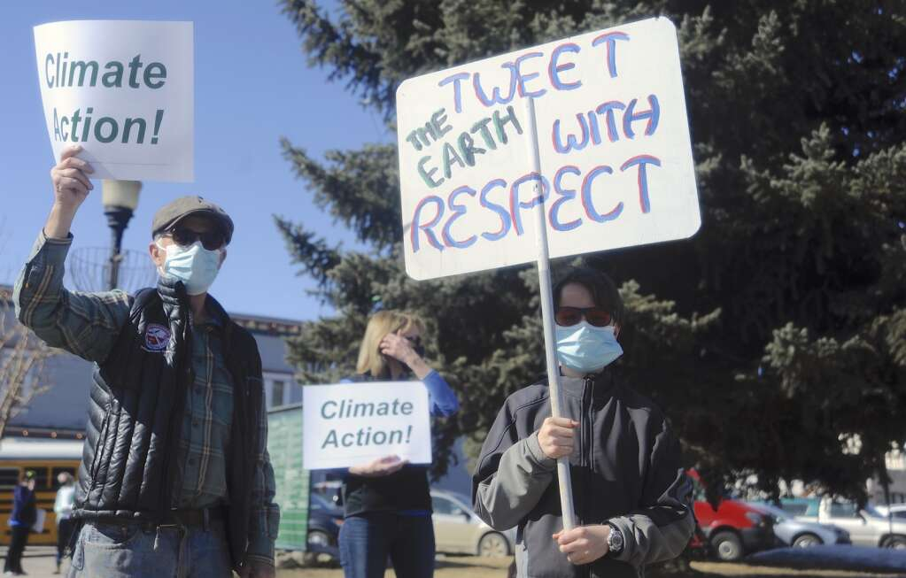Johnny Walker, left, and Lynx Beauregard, 12, participate at a Climate Action Rally at the Routt County Courthouse Lawn on Friday afternoon. (Photo By Shelby Reardon)