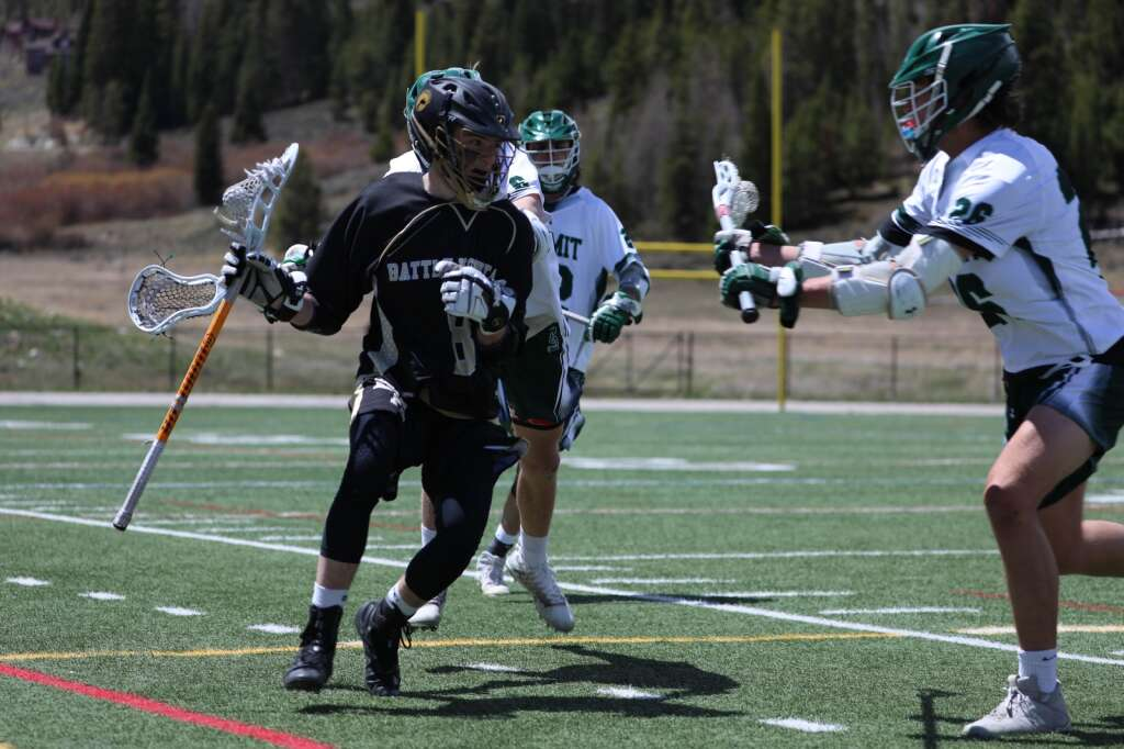 Summit senior Andrew Duxbury checks Battle Mountain's Leo Rothenberg during the Tigers' 11-8 loss to the Huskies on Saturday at Tiger Stadium in Breckenridge. | Photo by Ashley Low / Ashley Low Photography