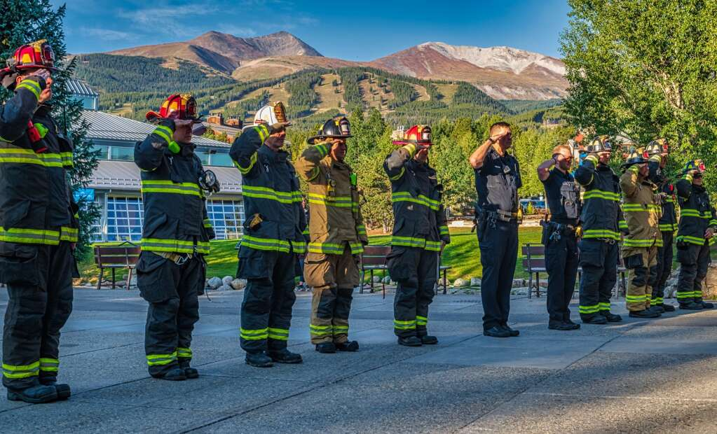 Firefighters from the Red, White & Blue Fire Protection District, as well as officers from the Breckenridge Police Department, salute in a circle on the Blue River Plaza on Sept. 11, 2021. The organizations hosted a small, brief ceremony to honor the 20th anniversary of 9/11.   Joel Wexler/For the Summit Daily News