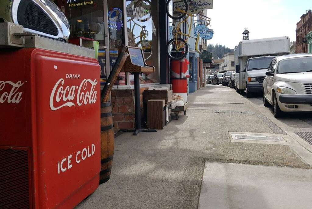 A Coca Cola sign sits on a street in downtown Placerville.