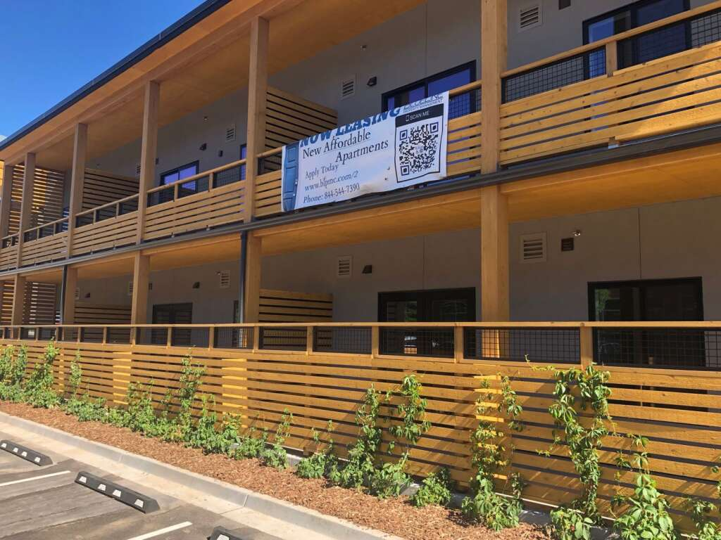 A banner hanging on the Red Hill Lofts invites applicants for the affordable housing units. About 150 applications have been received so far. | Scott Condon/The Aspen Times