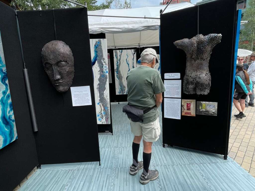 A man looks at a sculpture created by Breckenridge-based artist Levi Larkin. The booth features art from both Larkin and Breckenridge-based artist Andrea Kreeger at the Keystone River Run Village Art Festival on Saturday, July 24, 2021. | Photo by Jenna deJong / jdejong@summitdaily.com