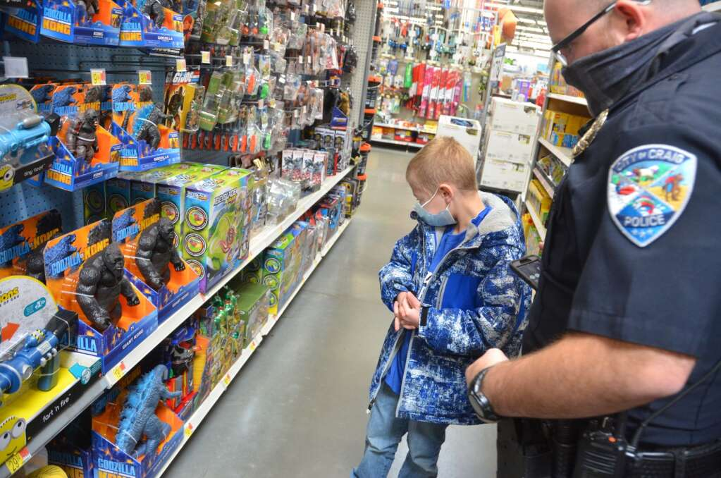 One of the kids works with an officer to help find a toy that he wants to buy