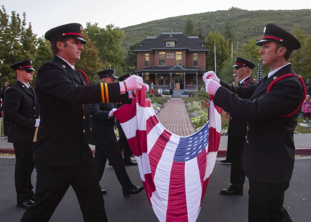 Members of the Park City Fire District Honor Guard, illuminated by the flashing red lights of a fire engine, fold the American flag in front of the Miners Hospital in City Park on Saturday morning during a ceremony marking the 20th anniversary of the Sept. 11 attacks. (Tanzi Propst/Park Record)