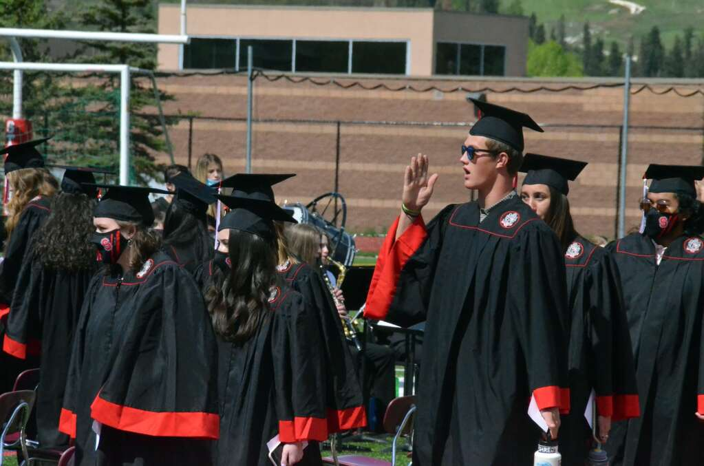 Alden Wade raises his hand to a friend and fellow graduate. (Photo by Bryce Martin)