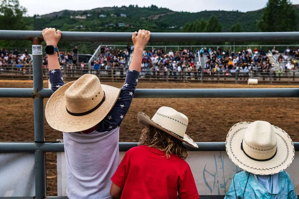 Young, aspiring cowboys hang on the gates at the Snowmass Rodeo on Wednesday, June 23, 2021. (Kelsey Brunner/The Aspen Times)