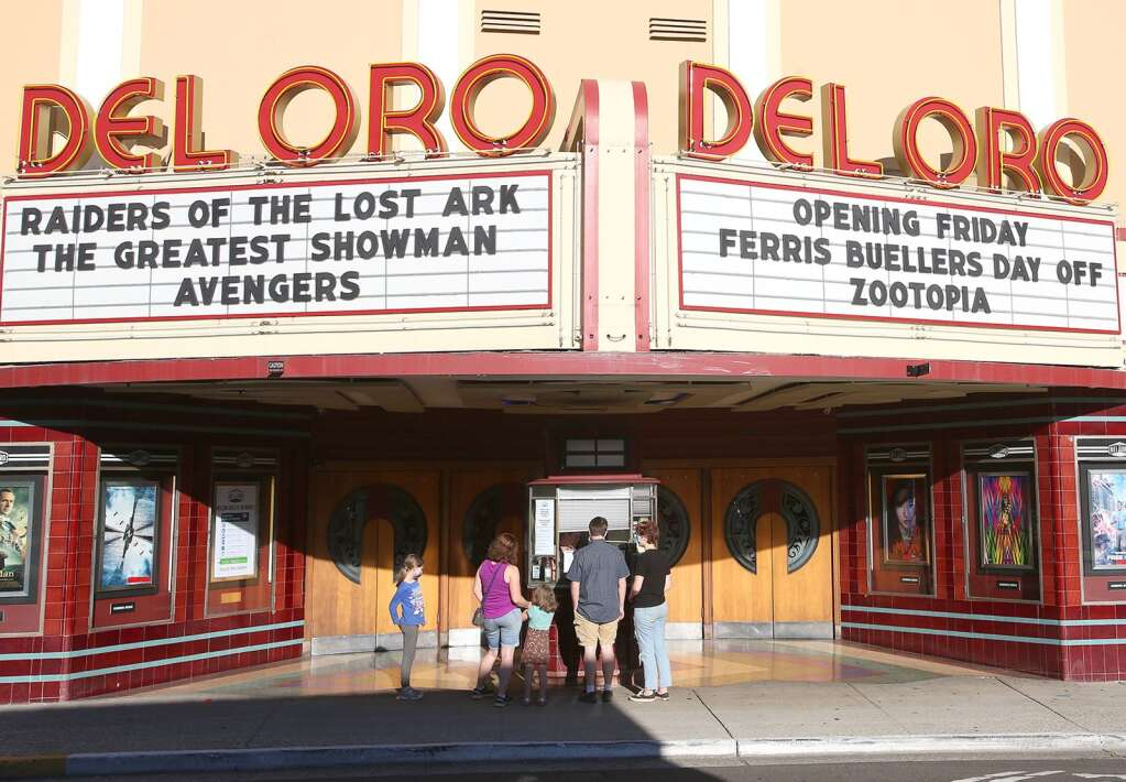 A family purchases their tickets from the Del Oro Theater box office for a show in late June. | Photo: Elias Funez