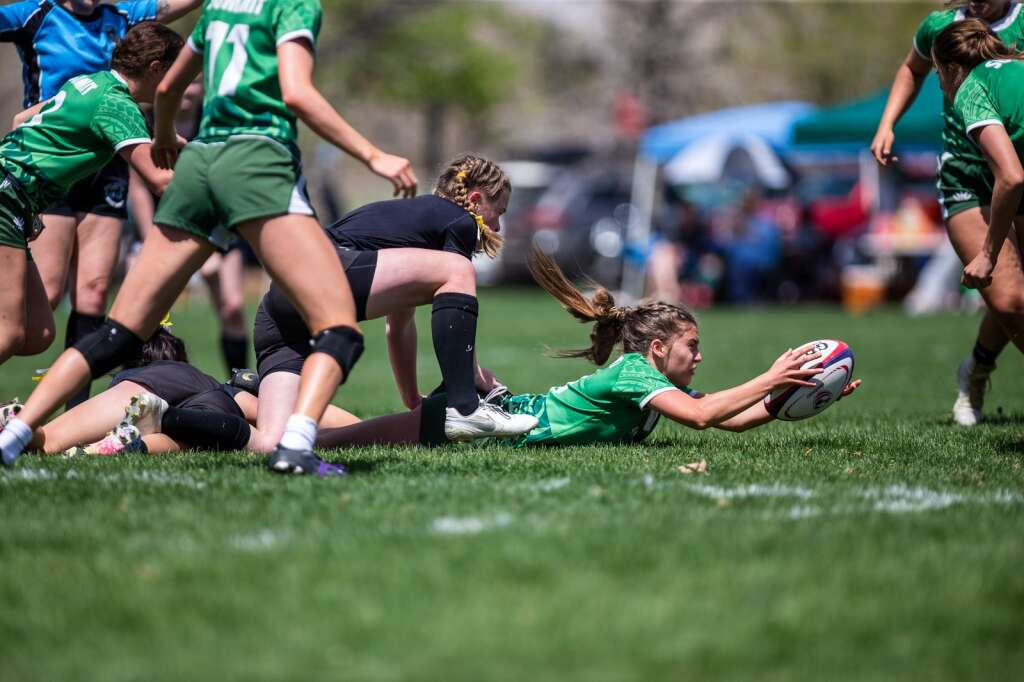 Bryton Ferrari dives to save the ball as a Monarch player tackles her during the first of three games played at the high school rugby state championship on Saturday, May 1, 2021, at Cook Park in Denver. The Summit High girls rugby team won their 13th straight state championship title. | Photo by Liz Copan / Studio Copan