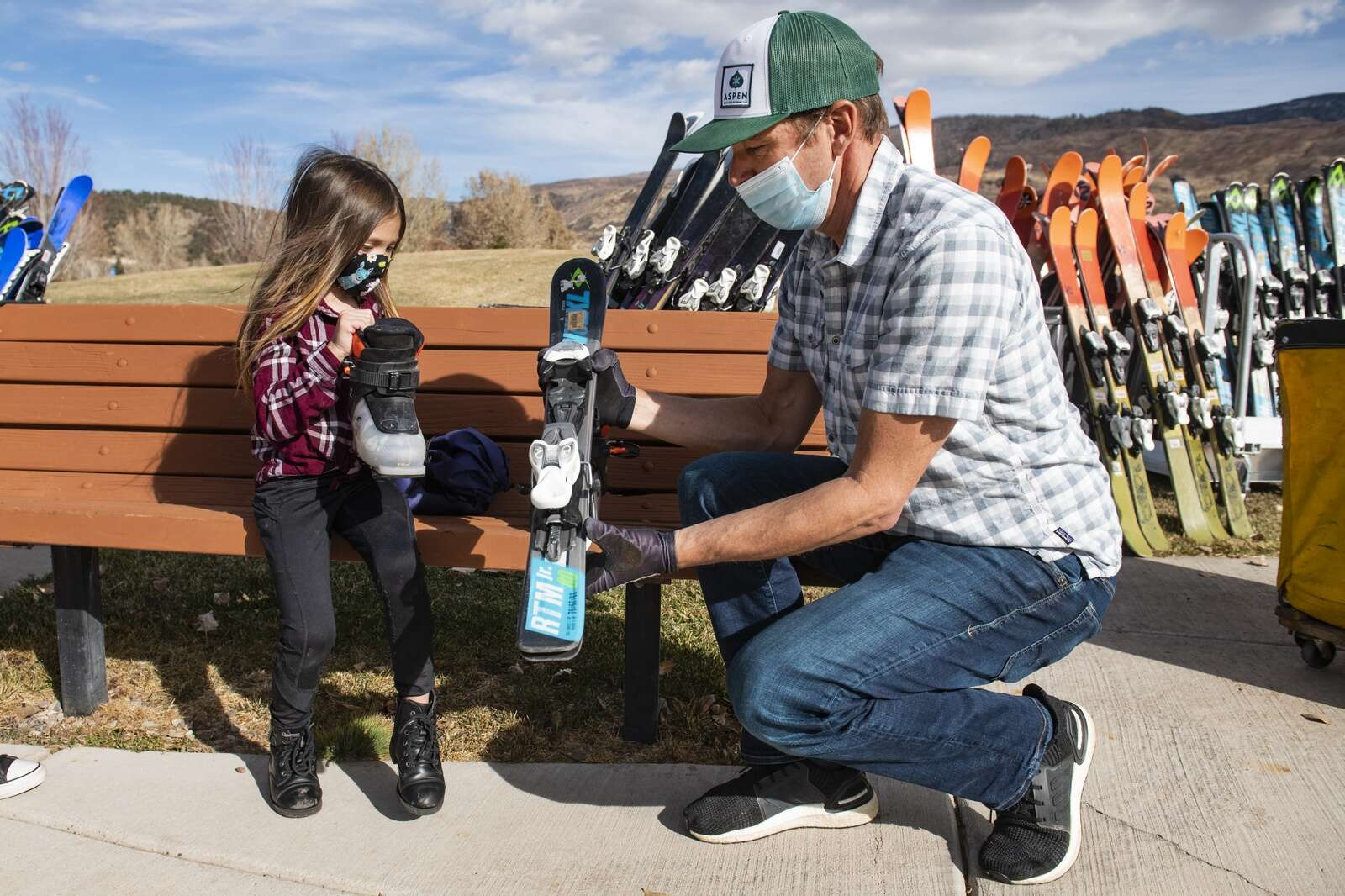Chris Davenport hands Aliyah Rivera, 6, her new pair of skis provided by Gorsuch and AVSC during the annual equipment day held at Crown Mountain Park in El Jebel on Wednesday, Nov. 18, 2020. It makes me so happy to do something uplifting and positive, said Davenport about the day. (Kelsey Brunner/The Aspen Times)