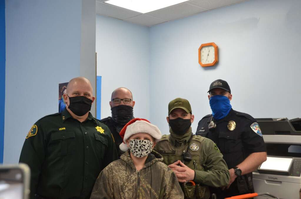 Adam Thomas Brown poses with the officers after getting his presents wrapped
